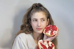 青少年的女孩用石榴果子 免版税库存图片