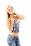 青少年的女孩美好白肤金发快乐享用在T恤杉美国旗子 库存图片