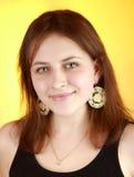 女孩的垂直的画象17岁在一黄色backgrou的 库存图片