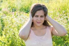 青少年的女孩结束他的耳朵和做鬼脸在痛苦中 免版税库存照片