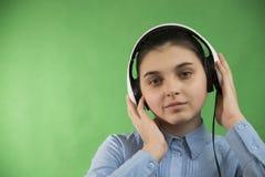 青少年的学校女孩听在耳机的音乐 库存图片