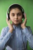 青少年的学校女孩听在耳机的音乐 免版税库存图片