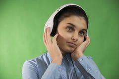 青少年的学校女孩听在耳机的音乐 免版税图库摄影