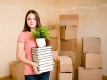 青少年的学院的女孩移动的房子,拿着堆书和植物 库存照片