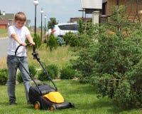 青少年的帮助割草坪 库存图片