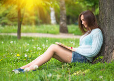 青少年的愉快的女孩在室外城市的公园读了一本书 免版税库存照片