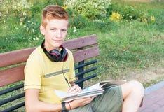 青少年的男孩与书坐长凳 免版税库存图片
