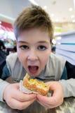 青少年的男孩吃汉堡包n咖啡馆 免版税库存照片