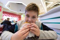 青少年的男孩吃汉堡包n咖啡馆 免版税库存图片