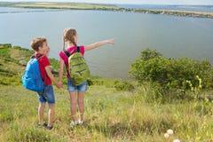 青少年的男孩和女孩有背包的在后面在远足,旅行,美好的风景去 图库摄影