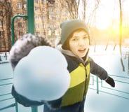 青少年的男孩在冬天做雪球户外 库存图片