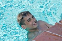 青少年的男孩在水池潜水并且游泳 免版税图库摄影