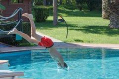 青少年的男孩在水池潜水并且游泳 库存图片