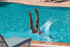 青少年的男孩在水池潜水并且游泳 免版税库存图片