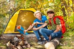 青少年的男孩坐露营地用香肠棍子 免版税库存照片