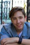 青少年的男孩外部画象  英俊的少年微笑和坐单独台阶 免版税库存图片