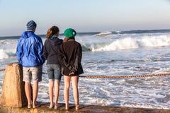 青少年的男孩女孩海滩波浪 库存照片
