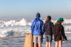 青少年的男孩女孩海滩波浪 库存图片