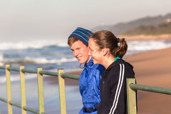 青少年的男孩女孩谈话时间海滩波浪 库存图片