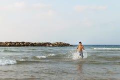 青少年的男孩沿海滩跑 免版税库存照片