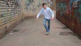 青少年的男孩跳舞,在砖墙背景的街道跳舞  股票视频