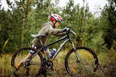 青少年的男孩运动员上升徒步有他的自行车的 免版税库存照片