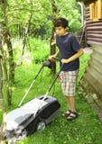 青少年的男孩移动的草草坪witm搬家工人 库存照片