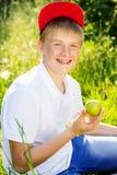 青少年的白肤金发的男孩拿着绿色苹果 免版税图库摄影
