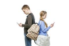 青少年的站立与手机的男孩和女孩 免版税库存照片