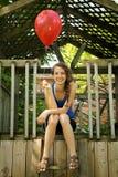青少年的藏品一个红色气球 免版税图库摄影