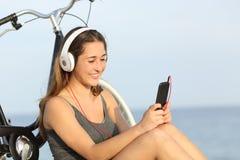 青少年的从一个巧妙的电话的女孩听的音乐在海滩 库存图片