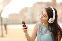 青少年的从一个巧妙的电话的女孩唱歌的和听的音乐 库存照片