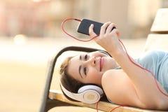 青少年的从在长凳的电话的女孩听的音乐 免版税图库摄影