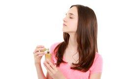 青少年的从瓶的女孩祈祷的香水 免版税图库摄影