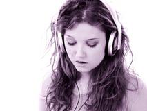 青少年美丽的女孩耳机的膝上型计算&# 免版税图库摄影