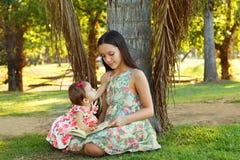 青少年逗人喜爱的姐妹和女婴阅读书 免版税图库摄影