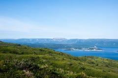 青山临近水反对高原在淡蓝的天空下 免版税库存照片