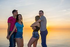 青年人、人和女孩是在海前面的容忍在su 免版税库存图片