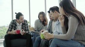 青年人不同种族的创造性的队变化编组队拿着咖啡杯和谈论遇见片剂的想法 股票录像
