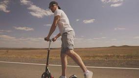 青年人乘驾滑行车 室外的活动 在空的领域和高速公路附近 年轻人乘坐滑行车 股票视频
