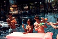 青年人公司从水枪射击入彼此在水池 游泳池党 免版税库存照片