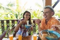 青年人吃中国面条愉快微笑的一起用餐在夏天大阳台 免版税库存图片