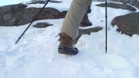 青年人在冬天在山,走在雪的背包徒步旅行者步行 股票录像