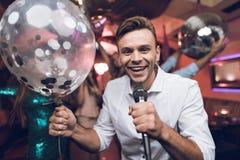 青年人在卡拉OK演唱获得乐趣在夜总会并且唱歌 在前景是一件白色衬衣的一个人 免版税库存图片
