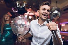 青年人在卡拉OK演唱获得乐趣在夜总会并且唱歌 在前景是一件白色衬衣的一个人 免版税库存照片