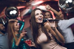青年人在卡拉OK演唱获得乐趣在夜总会并且唱歌 在前景是一件米黄礼服的一名妇女 库存照片