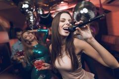 青年人在卡拉OK演唱获得乐趣在夜总会并且唱歌 在前景是一件米黄礼服的一名妇女 图库摄影