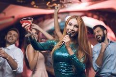 青年人在卡拉OK演唱获得乐趣在夜总会并且唱歌 在前景,一件绿色礼服的一名妇女 免版税库存照片
