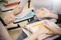 青年人在圈子坐,握手 免版税库存图片
