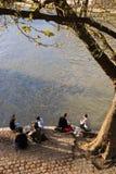 青年人在巴黎享受春天温暖,坐塞纳河的银行 免版税库存照片